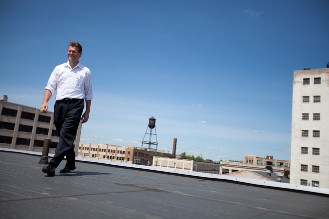 Garth Schultz walks on the roof of NextEnergy, the alternative energy incubator that houses his solar panels and lab space. Photo by Mike Ehrlich